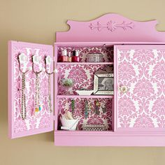 Retro Redo  A discarded display cabinet gained new life with lipstick-pink paint and sections of punchy damask paper inside and out.  Editor's Tip: Keep your jewelry organized by attaching clothes hooks and cup hooks to a wall-hung cabinet.