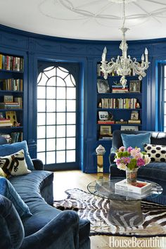 In the library, a pair of custom curved sofas is covered in a linen velvet from Lee Jofa with blue pillows in a velvet by Old World Weavers. The Warren Platner glass coffee table is from Knoll. The walls are in Benjamin Moore's Caribbean Azure.