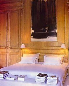 White bed, books, art, wood walls