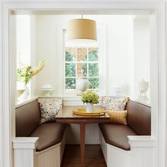 A beautiful brown and white eat-in kitchen with a garden view.