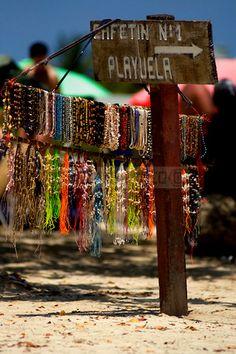 Un mostrador portátil de collares artesanales cuelga de un cartel en una orilla de Playuela, una playa de un cayo en el Parque Nacional Morrocoy. Falcón Venezuela