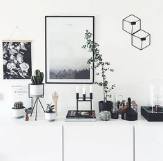 White drawers, white walls, broken up by green and dark metal black accessories and art