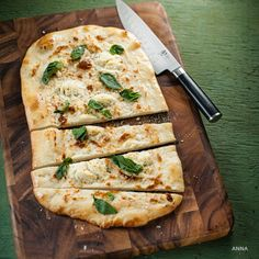 White pizza with basil and oregano. This beautiful pizza is garlicky and herbaceous. Served as a starter, or an entrée, this delicious recipe will bring friends together.