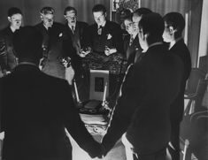 Thirteen magicians gather around a chair on which are a portrait of Houdini, two candles, a book, and handcuffs, for a midnight seance on Halloween, 1946, in Detroit, Michigan. From Atlantic Photo -http://www.theatlantic.com/photo/2015/01/detroit-in-the-1940s/384523/