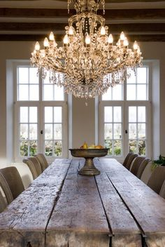 Mix and match a farmhouse style dining room table with an elegant chandelier.