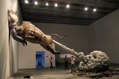 "This photo of Chinese sculptor Chen Wenling's ""What You see Might Not Be Real,"" comes via the Wall Street Journal of all places. This is because the bull represents Wall St and the man is Bernie Madoff. The sculpture is a critique of the financial crisis. It helps to know that fang pi in Chinese is both ""to fart"" and slang for ""to lie""."