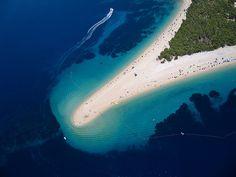 Playa sobre la Costa Dálmata. Se llama Zlatni rat, en la isla de Brac, una playa que tiene su forma en función del viento y las mareas. Aunque en lugar de palmeras, lo que hay son pinos junto a arenas claras, no falta el mar turquesa
