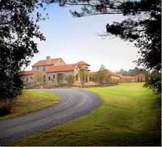 A Tuscan Dream Estate in Flora Mississippi~  Lynnstone is approached from a long, winding gravel driveway.  The house sits on 160 rolling acres with views of the treetops that surround the estate.  Kevin Harris, the architect, said the landscape reminds one of Tuscany with the hills and trees.  From this angle, the house looks like a small village with all its different rooftop heights and bell tower.