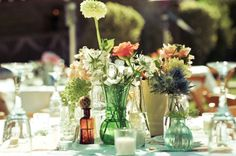 Mix-matched green and brown bottles with the flowers in the accent color