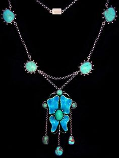 An Arts & Crafts silver necklace. The enamelled butterfly shape pendant with turquoise drops suspended from the chain with silver plaques also set turquoise. English. Circa 1900.