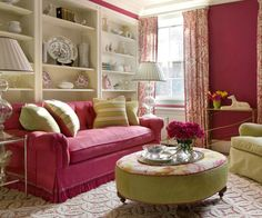 Eye-Catching Color Scheme: Magenta + Apple Green.   A hot pink tufted sofa, accented with dotted stripe green, pink, and cream pillows, pops against a gallery-like arrangement of ivory bookshelves. Pear green, a complementary hue to the deep pink, makes a strong statement in this space, with armchairs in a green cotton-linen blend and a round ottoman in a coordinating stargazer lily print. Batik-printed linen draperies bring lively pattern to the walls.