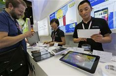 In this April 12, 2014 photo, staff members show the Chinese made tablets to a buyer in a booth at the Global Sources Spring China Sourcing Fair in Hong Kong. (AP Photo/Kin Cheung) ▼17Apr2014AP|China factories face new challenge as growth slows http://bigstory.ap.org/article/china-factories-face-new-challenge-growth-slows