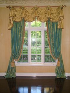 Closing drapes tied back and puddled on the floor, with fringe trim on the drape edges and tassel ties. Valance style is Kingston swags and cascades on a fluted wood pole. Valance details include button tabs along the top with small tassel ends as well as fringe edge along the valance hem. A very traditional, formal and European look.