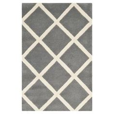 Hand-tufted wool rug with a diamond lattice motif.  Product: RugConstruction Material: WoolColor: Dark grey and ivoryFeatures: Hand-tufted Note: Please be aware that actual colors may vary from those shown on your screen. Accent rugs may also not show the entire pattern that the corresponding area rugs have.Cleaning and Care: Professional cleaning recommended