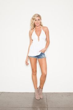 White halter top with low back, front cuts and even better, built in bra support. Throw this top on with a pair of denim shorts or spice it up with some white on white.