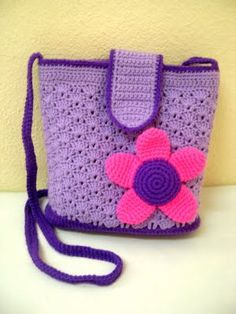 Purple crocheted bag with flower.