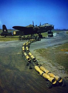 A bomb-train of sixteen 250lb bombs arriving to be loaded by the waiting Royal Air Force armourers into a Short Stirling bomber (s/n N6101) ...