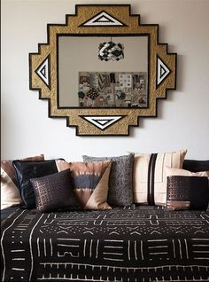 At left, a daybed strewn with Stone Textile pillows is presided over by an Art Deco–inspired mirror Mollen painted herself.