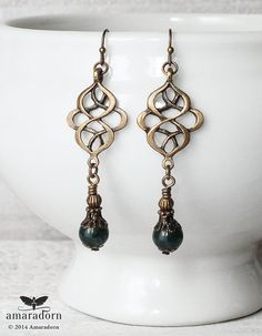These elegant vintage inspired earrings feature bronze finish ornate connectors which echo the organic style of the Art Nouveau period. They are