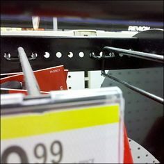 A narrow perforated metal rail adds a forward row of hooks to this display just below the Header Sign creating this Bar as Pegboard Extender for All-Wire Hooks. Perforated Metal, Metal Bar, Cutlery, Knives, Hooks, Surface, Display, Detail, Knifes
