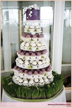 Tiers of purple cupcakes on a green bed of grass | Green Grass Wedding Reception Details For Spring