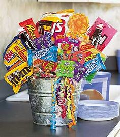 """You could satisfy the sweet tooth of everyone in the office with this bucket of great treats that everyone knows and loves. (And craves, too.)  Candy bars, lollipops, jellybeans and more arrive in a galvanized tin bucket decorated with bright curling ribbon.15"""" W x 20"""" H   Please note: All of our bouquets and gift baskets are hand-arranged and delivered locally by professional florists. This item may require additional lead time so same-day delivery is not available"""