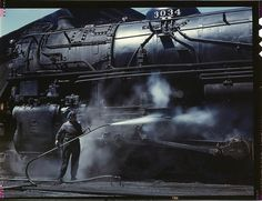 """Mrs. Viola Sievers, one of the wipers at the roundhouse giving a giant """"H"""" class locomotive a bath of live steam. Clinton, Iowa, USA, April 1943. Reproduction from color slide. Photo by Jack Delano. Prints and Photographs Division, Library of Congress."""
