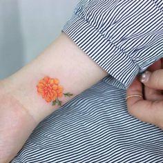 Marigold tattoo on the wrist.