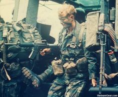 A Member of Company. L (Ranger), 75th Infantry, disembarks from a UH-1D helicopter during Operation Bushmaster.    Wearing an ERDL camouflage tropical combat uniform, the Ranger is armed with a CAR-15 (XM-177) rifle and uses 1-quart canteen covers to carry the magazines. He also wears a STABO harness.    Photo taken: August 1971
