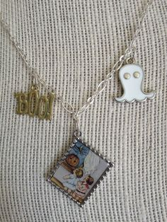 Halloween Necklace  Nostalgia is in the air... Two small children look out the window past the Jack-O-Lantern as the wind is carried inside. In the distance they see the crescent moon and they can hear the ghosts, boo. This piece is just too cute! One of a kind, I cannot make another.  Vintage inspired pendant, white ghost charm and gold boo charm attached to silver link chain necklace. Easy to use spring ring clasp.  Necklace measures 18 1/4 l. Pendant measures 1 1/2 l.  This piece will be…