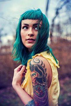 Ink / Portrait of young woman with blue hair and tattoos looking up over her shoulder.