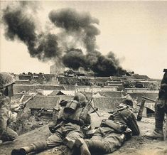 Japanese soldiers watch as smoke rises from a town. Hubei Province, China. 8th of June 1940.