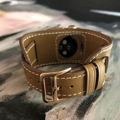 Caramel Brown Apple Watch Leather Cuff by Juxli Home.  Handmade, stylish leather strap with rose gold hardware on a 40mm Apple watch on a canvas with a black and gray painting. #juxlihome #applewatch #applewatchband #applewatchbands   #applewatchstrap   #applewatchseries4 #applewatchseries3 #applewatchcuff
