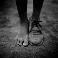 Photo by Dan Winters. Boy with One Shoe. Morocco, This could represent disorder in society; how we neglect those who need help and money the most and concentrate on our own greed. The whole system is disordered and this points such a fact out. Poverty Photography, Street Photography, Art Photography, Photography Portfolio, Black N White, Black White Photos, Black And White Photography, Natural Light Photography, Henri Cartier Bresson