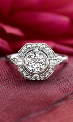 In this vintage-inspired engagement ring, a bezel-set center diamond floats above a halo of diamond accents bordered by an octagonal frame. Bezel-set baguette accents create a look of shimmering beauty