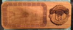 Manchester United Soccer field cribbage board cut on Cherry with removable tigerwood team logo for card and peg storage. Perfect gift for a soccer fan! Custom Metal, Custom Art, Cribbage Board, Manchester United Soccer, Soccer Fans, How To Remove, How To Make, Bamboo Cutting Board, Team Logo