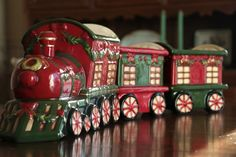 "Large Ceramic Train Set, by Hanna's Handiworks. Beautiful ceramic train set, hand-painted in classic rich red and green, perfect for displaying as a centerpiece or on a side table! Fill the cars with candy canes, decorative ornaments, utensils for a buffet, potpourri, nuts, candies...! Set measures approx 2 feet long (24 inches) when end to end. Train cars each measure 6"" long, 5"" wide, 6.25"" tall. Engine measures 11.5"" long, 5"" wide, 7.25"" tall. - The Weed Patch www.theweedpatchstore.com"