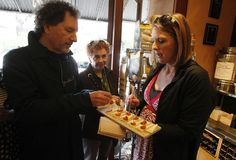 Walk and nosh: Three tasty walking food tours around the Bay  Lew Epstein, left, gets a cheese sample from tour guide Lauren Herpich, right, at the Rockridge Market Hall during a walking food tour of Oakland&'s Rockridge neighborhood