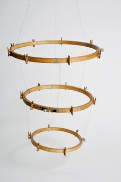 Embroidery Hoop Display mobiles. Made from wooden embroidery hoops, mini wooden clothes pins and wire. Can be used to display anything light-weight, like photos or other paper items.