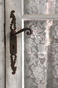Love the antique hardware, old, white door panel, & lace curtain ...