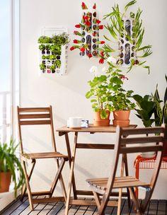 Tre VARIERA plastposeholdere henger på balkongveggen, der de brukes som blomsterpotter.