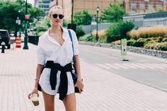 Candice Swanepoel en robe chemise blanche et lunettes de soleil