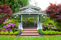 Large two-tiered white gazebo with brick floor set among lush gardens