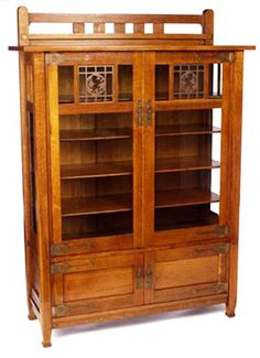 Stickley Brothers china cabinet, no.8644, two glass doors over two cabinet doors under a slatted plate rail, original copper hardware and overlaid copper design of a lion at top of each glass door | Arts and Crafts | Craftsman | Bungalow
