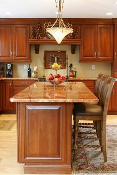 #Kitchen Idea of the Day: Traditional Cherry-Colored Kitchen Island with Seating and Chandelier. Love the rugs and wood backed bar stools.