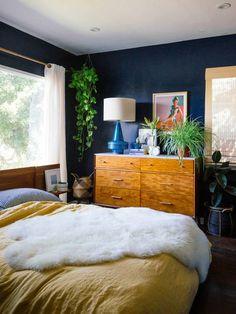 Eine Grüne Pflanze In Der Ecke, Ein Bett Mit Gelber Decke, Regal Mit  Zimmerpflanzen