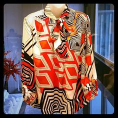 Jennifer Lopez geometric print blouse Jennifer Lopez blouse. Fun array of colors such as red, black, orange and white print top ties at neck. 3/4 length sleeve, cuffed at the end of each sleeve. Pic#4 shows the end of sleevs.  Gently used, good condition. Size Medium  100% polyester Jennifer Lopez Tops Blouses