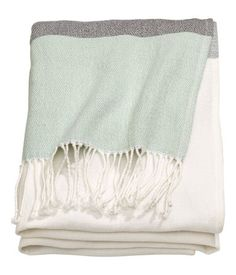 Blanket in woven, color-block cotton fabric with fringe at short sides.