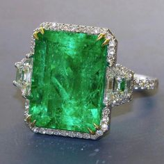 @dupuisauctions. Impressive Emerald ring of Colombian origin. Emerald is nearly 13.00 carats surrounded by small round diamonds and a pair of trapezoid-cut diamonds. Coming up this Spring at Dupuis Important Jewels Auction with pre-sale estimates of $50,000-$60,000.