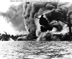 Pearl Harbor Attack, 7 December 1941   USS Arizona (BB-39) sunk and burning furiously, 7 December 1941. Her forward magazines had exploded when she was hit by a Japanese bomb.  At left, men on the stern of USS Tennessee (BB-43) are playing fire hoses on the water to force burning oil away from their ship   Official U.S. Navy Photograph, National Archives collection